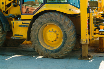 Close-up view of a dirty wheel of yellow heavy earth mover