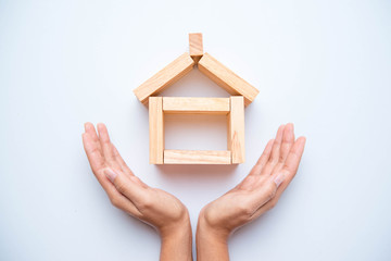 Hand arranging wood block as house. Real estate business concept.