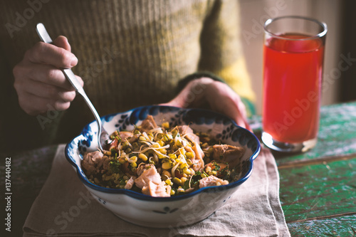 Woman In A Green Sweater Eating A Salad With Chicken And Beans
