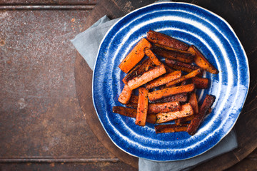 Roasted carrots on a blue plate on a brown table