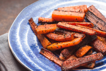 Roasted carrots on ceramic dish on a napkin
