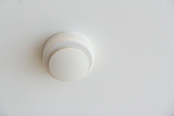 white smoke detector on ceiling for fire alarm system