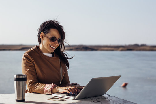 Pretty young woman surfing internet on laptop outdoors