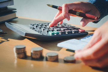 calculator and Financial data analyzing hand writing and counting in office on wood desk