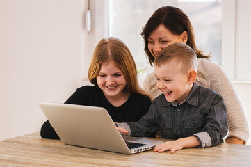 Mom and kids looking cartoons on laptop at home