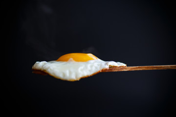 Photo sur Plexiglas Ouf Fried egg with a wooden spoon