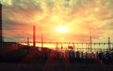 high voltage electric transmission tower at sunset.