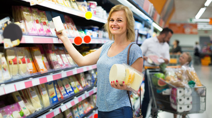 Portrait of woman holding assortment of cheese in grocery shop