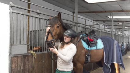 Frau zügelt ihr Hannoverander Pferd in der Stallgasse mit dem Zaumzeug