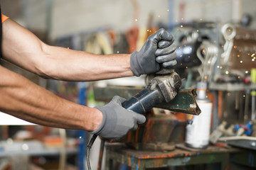 Close-up of a man's hands working with small radial saw. Jaen, Spain