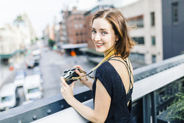 USA, New York City, smiling woman with camera on the High Line in Manhattan