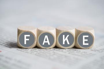"""Würfel mit Wort """"FAKE"""" auf einer Zeitung"""