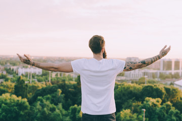Successful man looking up enjoying freedom with arms wide open- positive human emotion, feeling life perception, success, peace of mind concept.