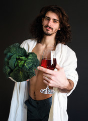 photo beautiful guy in a white drapery holding fresh green cabbage and a glass of wine in hand