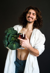 photo guy in white drapery holding fresh green cabbage and a glass of wine in his hands