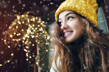 Outdoor close up portrait of young beautiful happy smiling girl posing on street. Model looking aside, wearing stylish winter hat. Snowfall, festive garland. City lifestyle. Copy, empty space for text