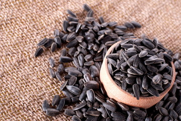 sunflower seeds in a wooden bowl on burlap background