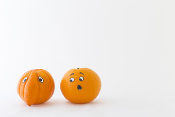 Fresh oranges with funny faces in front of white background. One orange has a huge nose