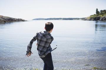 A boy throws rocks into the water; Victoria, British Columbia, Canada
