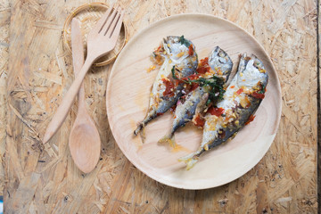 Mackerel fish fried topped spicy curry on wood dish