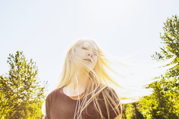 Beautiful young woman listening to music and singing along while swinging her long, blond hair outdoors in a city park; Edmonton, Alberta, Canada