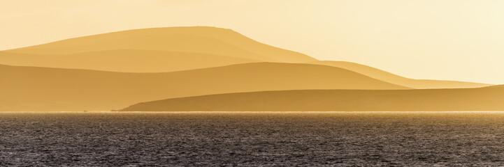 Sunrise over orange hills and blue ocean; Antarctica