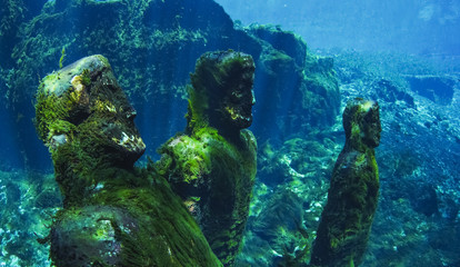 Movie props statues covered in green moss in freshwater spring