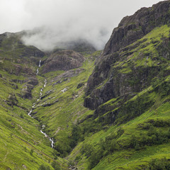 Clouds lying low over rugged and foliage covered mountains; Scotland