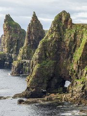 Rugged peaked cliffs and a natural arch along the coastline; John O'Groats, Scotland