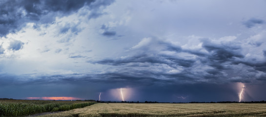 Storm clouds and lightning strikes over a rural landscape; Thunder Bay, Ontario, Canada