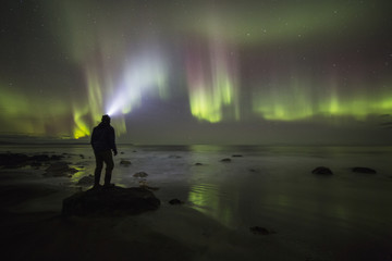 Northern lights dancing over the Langanes Peninsula and the Atlantic Ocean, Iceland, while a person stands on a rock watching them; Iceland