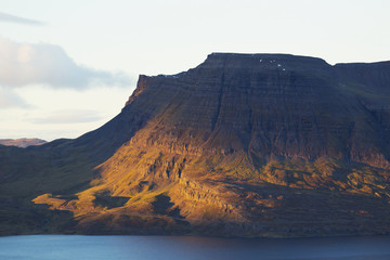 Late day sun illuminates the steep tiered cliffs in Iceland's Westfjords; Westfjords, Iceland