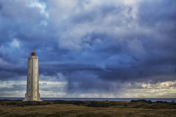 Lighthouse known as Malarrif on the Snaefellsness Peninsula with rain squall falling in the background; Iceland