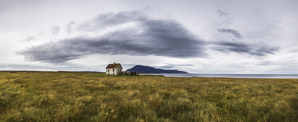 View of abandoned house on grassy landscape