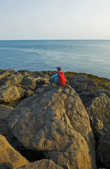 Hiker sits on a rock with a view of the shoreline, Bay of Fundy; Long Island, Nova Scotia, Canada