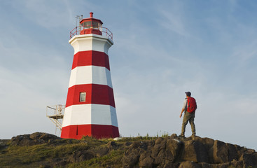 Hiker looking out over Brier Island Lighthouse, Brier Island, Bay of Fundy; Nova Scotia, Canada