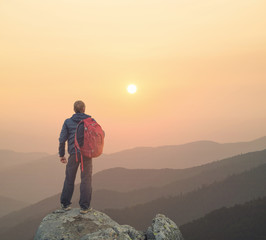 Tourist on the peak of high rocks during sunset. Sport and active life concept..
