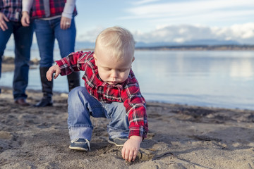 A young toddler gets his hands dirty playing with sand on the beach while his parents look on from the background; Surrey, British Columbia, Canada