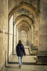 Pedestrian walking by Winchester Cathedral; Winchester, Hampshire, England