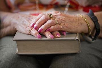 A senior woman's hands folded on a hard cover book; Devon, Alberta, Canada