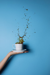 Hand of cropped unrecognisable woman holding cup of coffee in splash.
