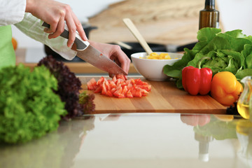 Photo sur Plexiglas Cuisine Closeup of human hands cooking vegetables salad in kitchen on the glassr table with reflection. Healthy meal and vegetarian concept
