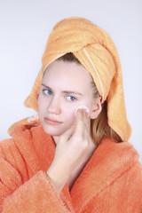 Teenager in bathrobe and towel on head. Skin moisturize using cotton pad