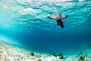 Woman snorkeling by sea bed, Staniel Cay, Bahamas, Caribbean