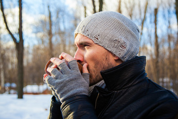 Handsome young man is traveling. He is looking forward in the forest at the nature. Blured background. He is drinking hot tea.