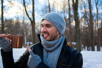 Handsome young man at the park in winter. He is looking forward, take a cup of coffee and smiling. Blured background. He is froze.