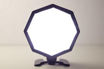 Ein achteckiges ausgelöstes Blitzlicht steht frei auf einem hellen Untergrund.