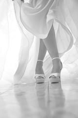 dettaglio scarpe e abito da sposa in foto bianco e nero su sfondo tenda - le gambe sono incrociate