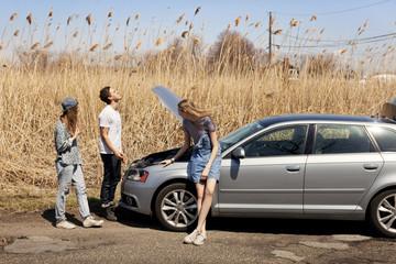 Friends checking car engine roadside