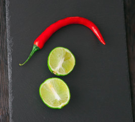 pepper and lime on black stone board
